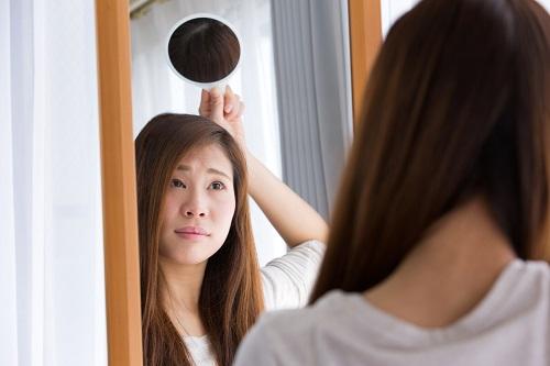 手鏡で頭頂部を見る女性